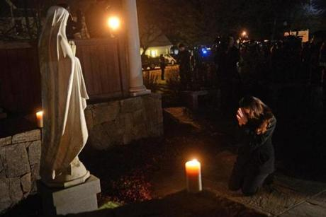 A woman prayed at the vigil at St. Rose Church in Newtown.