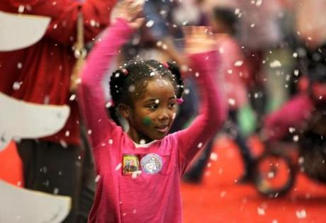 The Evaporative Snow flying from the blower at the entrance to the Winter Wonderland held the attention of Michaela Alston-Reed, 7, during the Christmas in the City party for homeless mothers and their children at the Boston Convention & Exhibition Center.