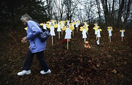 A woman walked away after leaving flowers near one of 27 wooden angel figures placed near the Sandy Hook School.