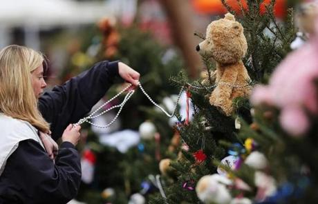 Kat Donohue of Newtown helped to decorate donated Christmas trees placed in front of the Sandy Hook School.