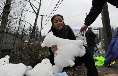 A woman placed stuffed animals at a memorial for the victims in Newtown, Conn.