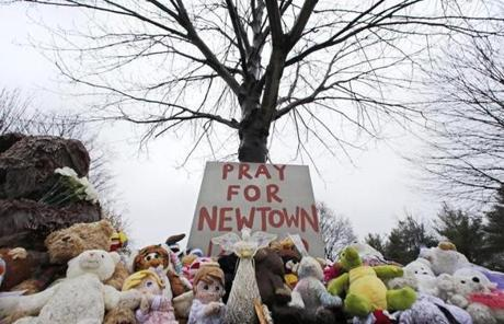 A sign among stuffed animals called for prayers near the Newtown Village Cemetery.