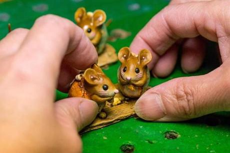 Small mice are placed on a base by Lynn Hau in the mounting room at Wee Forest Folk in Carlisle.