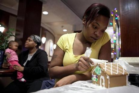 Laquita Bullock decorates a gingerbread house for her room at Home Suites.