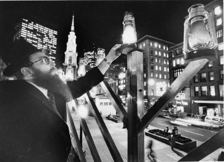 December 18, 1984:  Rabbi Chaim Prus, the director of Chabad House of Greater Boston on Commonwealth Ave., an educational center for young people, adjusts a Chanukah light atop a 22-foot menorah on Boston Common along Tremont St. He uses a cherry picker for the ceremony during which Boston Mayor Ray Flynn helped light 2 of the lights. This was the second year of the first public menorah in Boston.