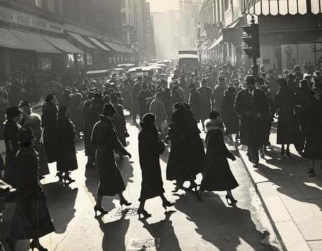 Year unknown: Busy Christmas shoppers were silhouetted in the late afternoon light as they crossed Washington Street outside the two big department stores, Filene's and Jordan Marsh.