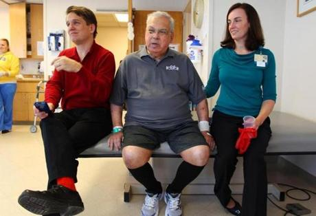 Keith Lockhart (left), the mayor, and physical therapist Cara Brickley listened to a Christmas song.