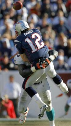Tom Brady was blasted by Miami defensive end Kevin Carter before delivering this pass.