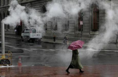 A woman walked in the rain as steam hovered in Copley Square.