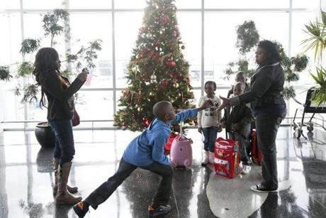 Kemi Ogunsaya (left) gathered family members together for photos in front of a Christmas tree near Terminal A at Logan Airport on Sunday. Her son, Charles, 10, handed a camera to Victoria Kayode. All were traveling from London, England, to visit family in Indiana, and had a layover in Boston.