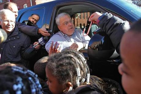 Boston Mayor Thomas M. Menino greeted children getting gifts at the Catholic Charities Teen Center at St. Peter's on Christmas Eve.