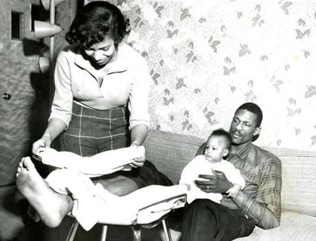 April 8, 1958:  Bill Russell and his five-month-old son, William Jr., looked on Russell's wife, Rose, tended to his right ankle. The injury suffered in the third game of the playoff series against St. Louis resulted in a badly sprained ankle, which doomed the Celtics' chances against the Hawks. Even though Russell returned to action, he was limping badly could not contain the Hawks' Bob Petit, who scored 50 points in the sixth and decisive game.