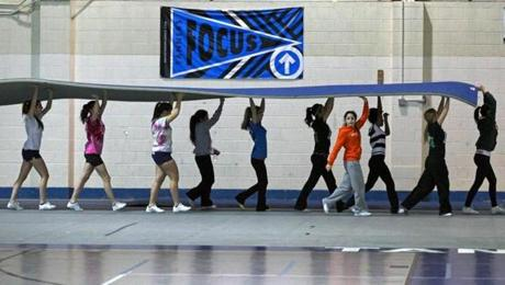 Members of the cheerleader and gymnastics teams helped move mats at Peabody Veterans Memorial High School gym during the holiday break.