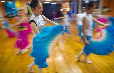 Boston, MA - 12/26/2012 - Chu Ling Dance Academy - Eva Gee, cq, 14, of Allston, MA practiced with a large fan during one of the dances. Young dancers practiced traditional and contemporary styles of Chinese dance at Chu Ling Dance Academy in Chinatown in preparation for their first Night performance at the FedEx Family Festival. Photo by Dina Rudick/Globe Staff