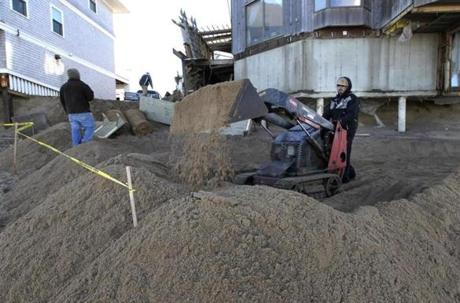 Workers moved sand in front of damaged houses on the beach in an effort to protect them from the next high tide.
