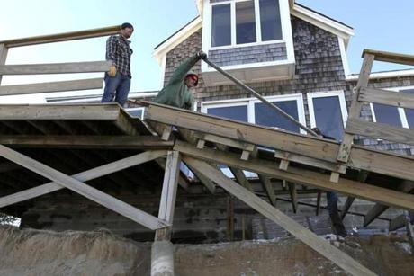 Graham and Ian McKay dismantled the damaged beachside deck on their family home on Plum Island as high tides continued to erode the beach.