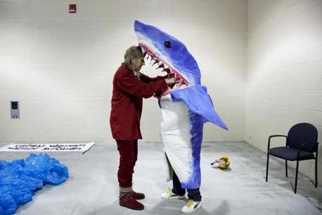 New York artist Pat Oleszko, left, helped Osmar Ramos-Caballero of Holyoke with his costume of a BP employee being eaten by a shark as the