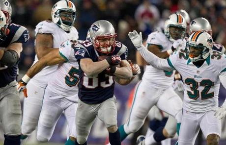 Wes Welker protected the ball as he was chased by Dolphins defenders.