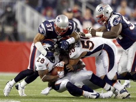 Rodney Harrison, top,  stopped Broncos running back Michael Pittman during the first quarter.