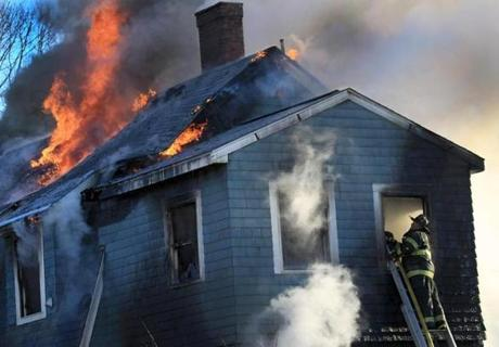Lieutenant Dennis Russo of the Revere Fire Department took to a ladder as firefighters from surrounding towns responded to a multiple-alarm fire in Swampscott.
