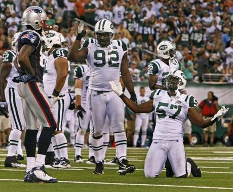 Jets linebacker Bart Scott (57) has some fun at the expense of Randy Moss after a Jets interception.