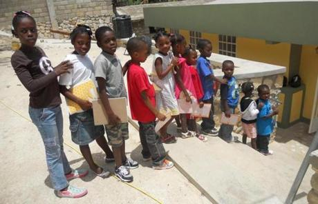 Youths in Haiti lined up the new orphanage built by Needham's Alliance for Children Foundation