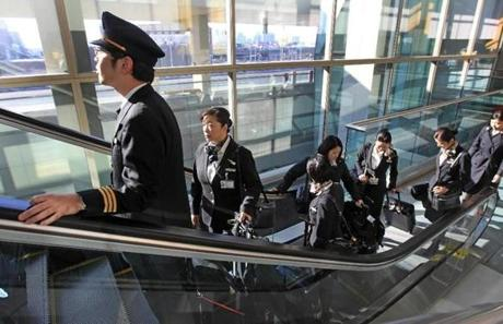Japan Airlines crewmembers depart Terminal E at Logan Airport after a fire was discovered on their plane moments after landing from Tokyo.