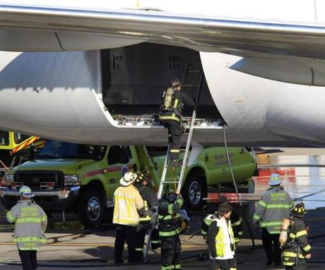 Massport firefighters enter into the cargo area of a Japan Airlines 787 Dreamliner jet. A fire was discovered on the plane shortly after its arrival at Logan Airport.