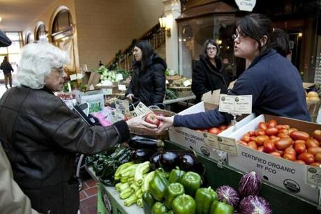 Katey Tobin of Enterprise Farm sells an apple to Margaret McCormick of Brookline at the Brookline Winter Farmer's Market.