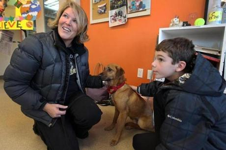 Laura Castergine and her 9-year-old son Griffin pet Bailey, a rescue dog she found in her Melrose yard and helped return to the Northeast Animal Shelter in Salem