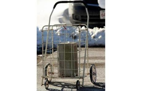 A metal cart with a concrete cylinder block in South Boston.