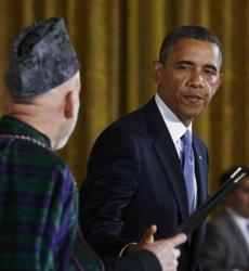 US President Barack Obama reached out to shake hands with Afghan President Hamid Karzai.