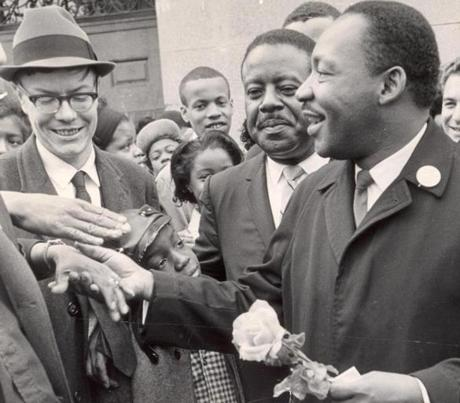 April 22, 1965: The wife of the Rev. Virgil Woods (not visible) presented a flower to the Rev. Martin Luther King Jr.  Woods and his son, Bobby Woods, were also in the crowd around King.