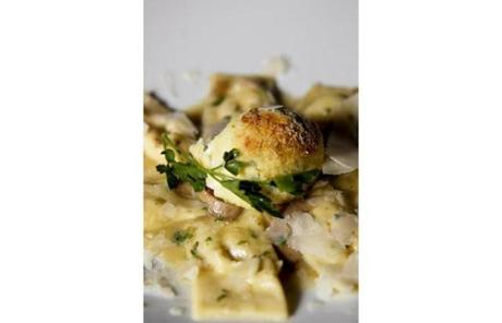 Ricotta gnudi, surrounded by pillow ravioli stuffed with ricotta.