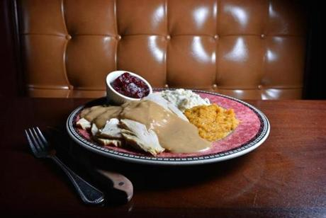 The New England roast turkey dinner features sliced turkey breast, homemade stuffing with squash, mashed potato, and gravy.