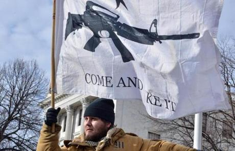 Nick M. held a flag with an assault rifle during a rally against gun control on the steps of the Statehouse.