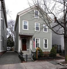 This house is now a fully renovated free-standing single-family with sunny rooms, off-street parking, and a small lawn.