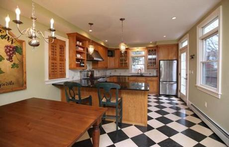 The dining room has a chandelier and leads to the kitchen, with its birch cabinets above dark countertops.
