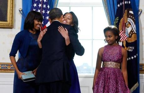 President Obama received a hug from daughter Malia as Michelle Obama and Sasha Obama looked on.