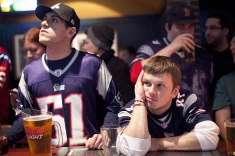 1/20/2013 - Boston, MA - Cask 'n Flagon sports bar - Paul Rowan, cq, right, of Dorchester, and Ben Dover, cq, left, of Braintree, react to the final moments of the game. Patriots fans were disappointed, enraged and often in tears as their team lost to the Baltimore Ravens, 28-13, in the AFC championship. Football fans of all stripes packed the Cask 'n Flagon sports bar in Kenmore Square to watch the AFC championship between the Baltimore Ravens and the New England Patriots on Sunday evening, January 20, 2013. Story by Matt Rocheleaum/Globe Correspondent. Photo by Dina Rudick/Globe Staff.