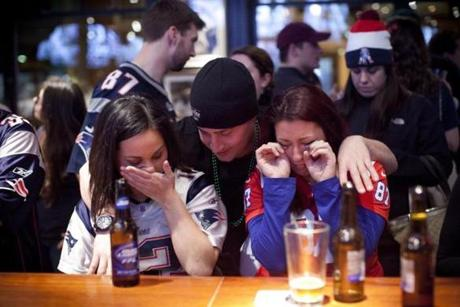 Timothy Pesa of Brighton comforted Kristin Feltz (left) and Danielle Shiner (right) , both also of Brighton, at the Cask 'n Flagon sports bar in Kenmore Square as the Patriots' season ended in a loss to the Baltimore Ravens, 28-13, in the AFC championship game.