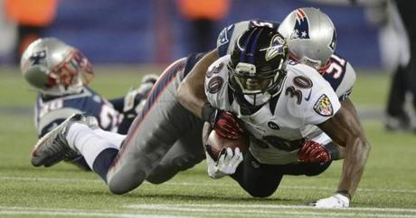 Baltimore Ravens running back Bernard Pierce is tackled by New England Patriots linebacker Jerod Mayo.