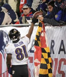 Baltimore Ravens receiver Anquan Boldin hands the ball to a Ravens fan after catching a touchdown pass in the fourth quarter.