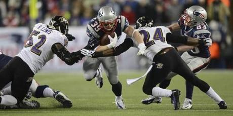 New England Patriots running back Danny Woodhead runs with the ball as Baltimore Ravens inside linebacker Ray Lewis (left) and Baltimore Ravens cornerback Corey Graham reach in for the tackle and block out New England Patriots receiver Wes Welker.