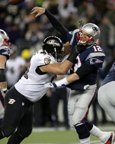 Patriots quarterback Tom Brady takes a hit as he gets off a pass late in the fourth quarter.