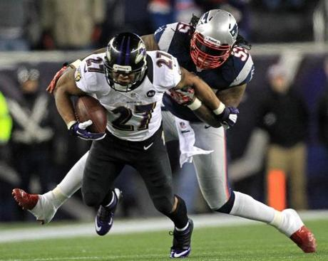 Baltimore Ravens running back Ray Rice breaks loose for a first down run as New England Patriots middle linebacker Brandon Spikes tries to corral him during the first quarter.