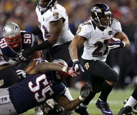 Baltimore Ravens running back Ray Rice breaks through the Patriots line for a long gain in the first quarter.