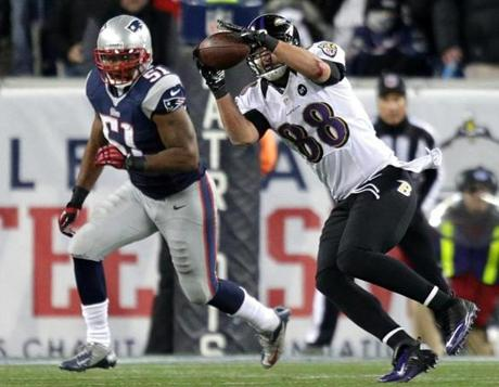 Baltimore Ravens tight end Dennis Pitta pulls in a pass in front of New England Patriots linebacker Jerod Mayo during the third quarter.