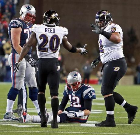 Ravens Ed Reed and Haloti Ngata celebrate over Patriots quarterback Tom Brady after he couldn't complete a fourth-down pass.