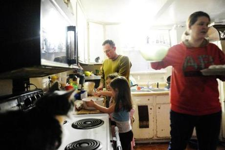 Christopher Carter helped cook dinner with his daughter, Sammy, 6 (center), niece, Gracie, 4, and his wife, Mary Ellen.